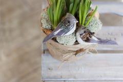 Dois pássaros decorativos estão sentando-se em um potenciômetro de flor com flores Imagem de Stock Royalty Free