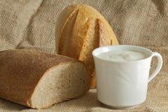 Dois pães com o copo do creme ácido na lona ensacam Imagem de Stock