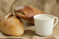 Dois pães com o copo do creme ácido na lona ensacam Fotografia de Stock