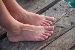 Dois pés das mulheres junto em uma plataforma do cais Fotografia de Stock