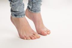 Dois pés desencapados que estão a ponta do pé no assoalho Foto de Stock Royalty Free
