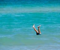 Dois pés que colam acima fora do oceano calmo azul bonito imagem de stock