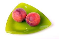 Dois pêssegos em uma placa triangular Foto de Stock