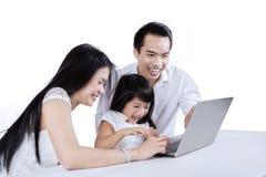 Dois pais ajudam sua filha Fotos de Stock