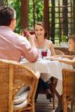 Dois pais que bebem o vinho tinto que comemora o aniversário de seu filho imagens de stock royalty free