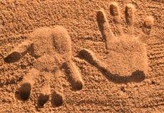 Dois palmprints na areia fotos de stock