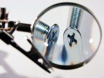 Dois parafusos sob um magnifier. Verific a qualidade. Fotos de Stock Royalty Free