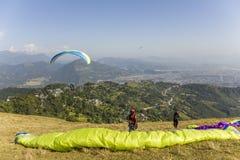 Dois paragliders no montanhês antes de decolar contra o contexto de um vale da montanha e de voar fotos de stock royalty free