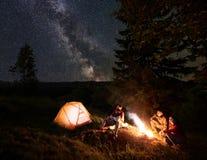 Dois pares aproximam a fogueira na noite nas madeiras que apreciam o céu estrelado fotos de stock