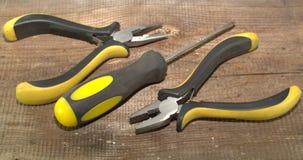 Dois pares de alicates com punhos isolados e uma chave de fenda em um fundo de madeira Imagens de Stock Royalty Free