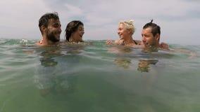 Dois pares de amigos que têm a natação do divertimento na câmera pov da ação do mar de povos brincalhão novos agrupam junto na pr vídeos de arquivo