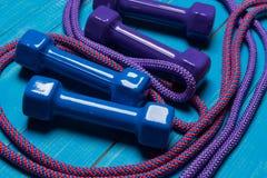 Dois pares de gantelae em placas, no azul e em pesos azuis do lilás e em torno da corda de salto lilás e cor-de-rosa, esporte do  Fotos de Stock Royalty Free