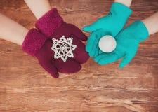 Dois pares de mãos das mulheres fizeram malha os mitenes que guardam um brinquedo do Natal em um fundo de madeira fotografia de stock royalty free