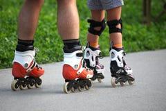 Dois pares de pés em patins de rolo Foto de Stock Royalty Free