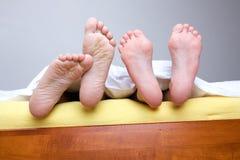 Dois pares de pés na cama Imagens de Stock