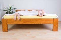 Dois pares de pés na cama Fotos de Stock