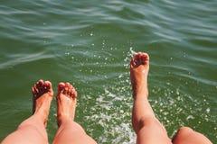 Dois pares de respingo dos pés na água fotos de stock