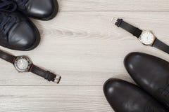 Dois pares de sapatas de couro pretas do ` s dos homens e dois relógios de pulso Imagens de Stock Royalty Free