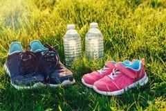 Dois pares de sapatilhas e de garrafas da água na grama verde fora no por do sol fotografia de stock