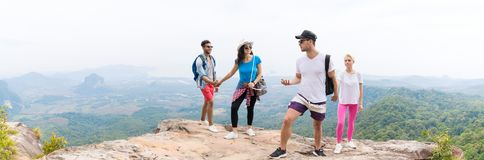 Dois pares do turista com a trouxa na fala superior da montanha sobre a opinião bonita do panorama da paisagem imagem de stock