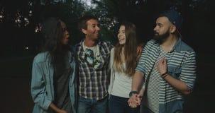 Dois pares dos amigos alegres do moderno estão falando, rindo durante sua caminhada da noite no parque filme