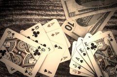 Dois pares e três de cartões de um pôquer do vintage do tipo com dinheiro em um fundo de madeira Imagens de Stock