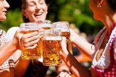 Dois pares felizes que sentam-se no jardim da cerveja Fotografia de Stock Royalty Free