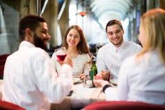 Dois pares felizes que sentam-se no restaurante exterior Foto de Stock Royalty Free