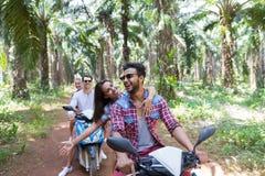 Dois pares novos que conduzem a bicicleta do 'trotinette' em Forest Young Group Of People tropical que faz a viagem por estrada n Foto de Stock