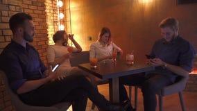 Dois pares novos que sentam-se na tabela e que olham nos telefones filme