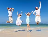 Dois pares que comemoram na praia no Natal Imagem de Stock