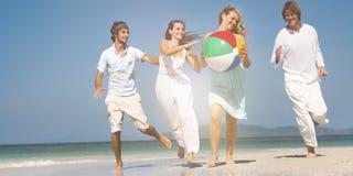 Dois pares que relaxam no conceito da praia imagens de stock royalty free