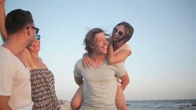 Dois pares que riem perto do mar durante horas de verão Fora retrato do grupo novo feliz de amigos que apreciam a praia video estoque