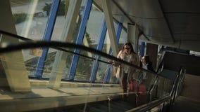 Dois passageiros das mulheres no aeroporto vão acima da escada rolante ao segundo andar vídeos de arquivo
