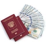 Dois passaportes vermelhos e cem notas de dólar em um fundo branco imagens de stock