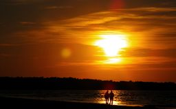 Dois pelo mar contra o sol imagens de stock royalty free
