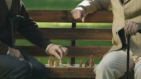 Dois pensionista que jogam a xadrez no banco de parque, estratégia do jogo, exercício do cérebro, passatempo filme