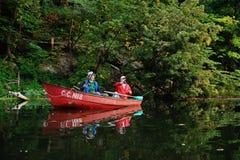 Dois pescadores em um barco com as varas de pesca que travam peixes Imagem de Stock