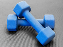 Dois pesos azuis do dumbell em uma esteira preta aberta da ioga do exercício Foto de Stock Royalty Free