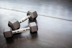 Dois pesos do metal no assoalho preto no gym eq da aptidão do esporte Fotografia de Stock Royalty Free