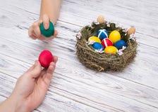 Dois pessoas que guardam ovos da páscoa coloridos da galinha em um conceito de madeira branco do fundo do jogo e na tradição na l fotografia de stock