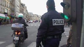 Dois polícias no tráfego de controlo do dever, pedestres que esperam para cruzar a estrada filme