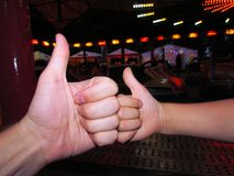 Dois polegares acima de uma mão pequena e adulta como fotos de stock