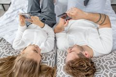 Dois povos agradáveis que apreciam seu tempo ao descansar na cama com dispositivos fotos de stock royalty free
