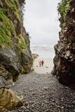 Dois povos andam na praia entre grandes rochas Fotos de Stock Royalty Free