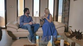 Dois povos bonitos que falam e que relaxam no sofá na sala de visitas vídeos de arquivo