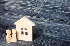 Dois povos estão estando perto da casa Figuras de madeira da pessoa Fotografia de Stock