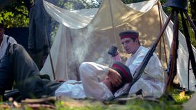 Dois povos militares que descansam em uma terra imagens de stock