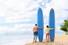Dois povos que estão com surfboars na praia imagem de stock