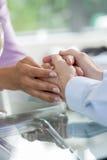 Dois povos que guardam as mãos para o conforto Imagem de Stock